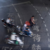 Asia, China, Shanghai, Elevated view of bicycle and motor scooter traffic riding past Chinese characters painted in traffic lanes on downtown streets