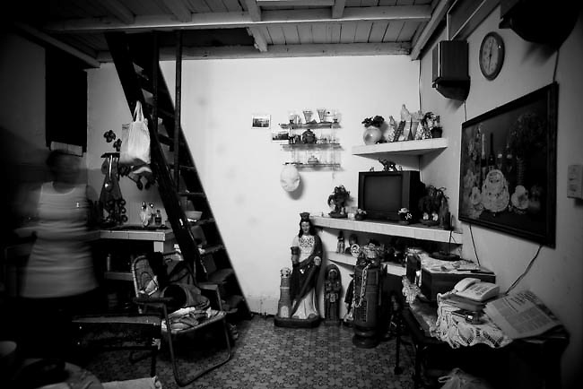 America, Cuba, Havana.  A woman inside her house in old havana, most of the figures are related with santeria religion. -06.07.2008, DIGITAL PHOTO, 49MB, copyright: Alex Espinosa/Gruppe28.