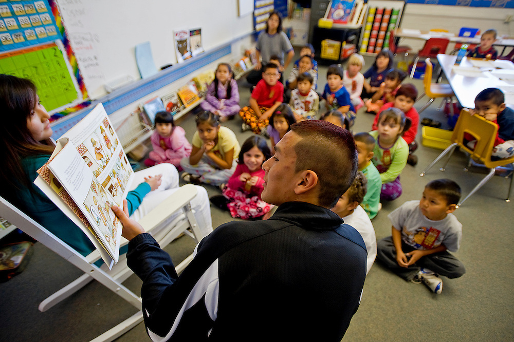 102710       Brian Leddy.Gallup High School senior Cody Bitsily reads to a group of first-graders at Roosevelt Elementary School on Wednesday. Several members the basketball team spent the morning reading books to students as part of a community service project.