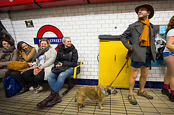 A man waits on the platform at Bond Street tube station as he takes part in No Trousers on the Tube day, in London.