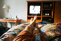 A first peson view of a mans legs relaxing on a bed in a hotel room watching the TV with a remote control on his lap.