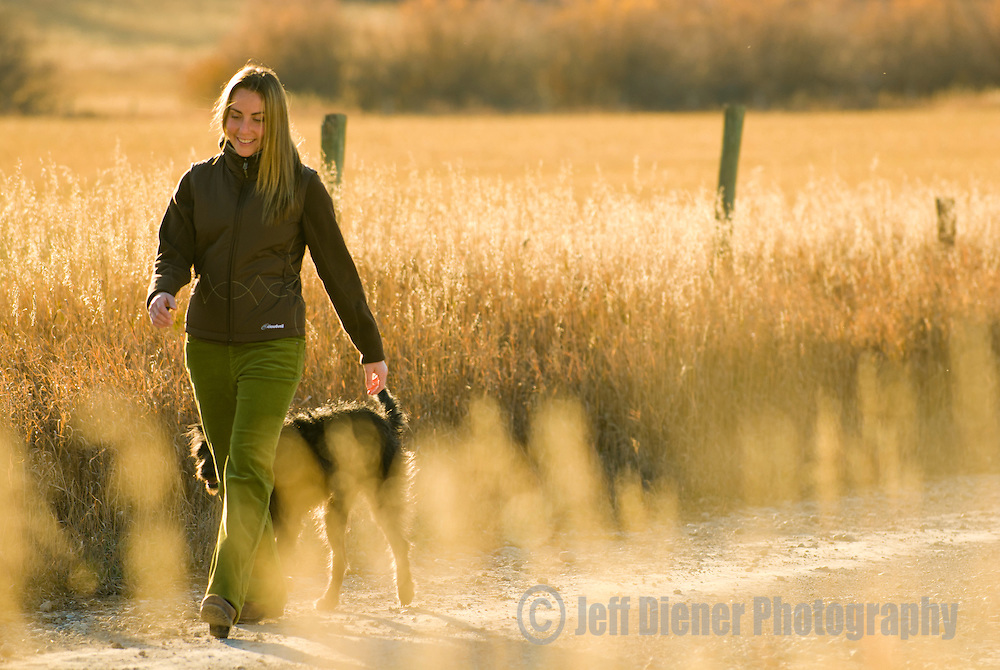 A young woman and her dog stroll along a country road in Teton Valley, Idaho.