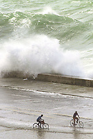 Two men ride a bicycle in the Havana's Malecon, facing the intense waves on Thursday November 20, 2003, in Havana, Cuba. The winds coming from the North transform Havana's view, every winter season. (AP Photo/Cristobal Herrera)