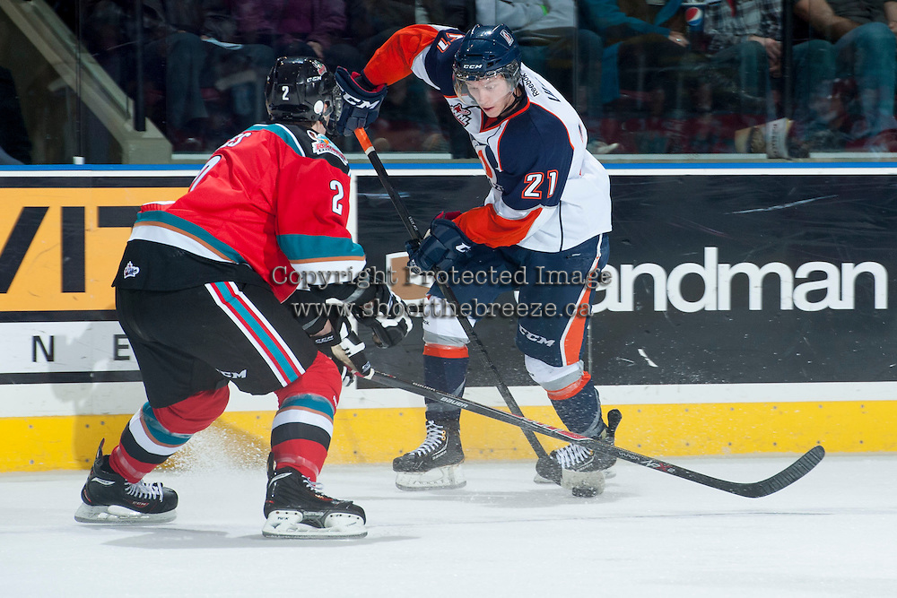 KELOWNA, CANADA - NOVEMBER 30: Cole Ully #21 of the Kamloops Blazers handles the puck while checked by Jesse Lees #2 of the Kelowna Rockets on November 30, 2013 at Prospera Place in Kelowna, British Columbia, Canada.   (Photo by Marissa Baecker/Shoot the Breeze)  ***  Local Caption  ***