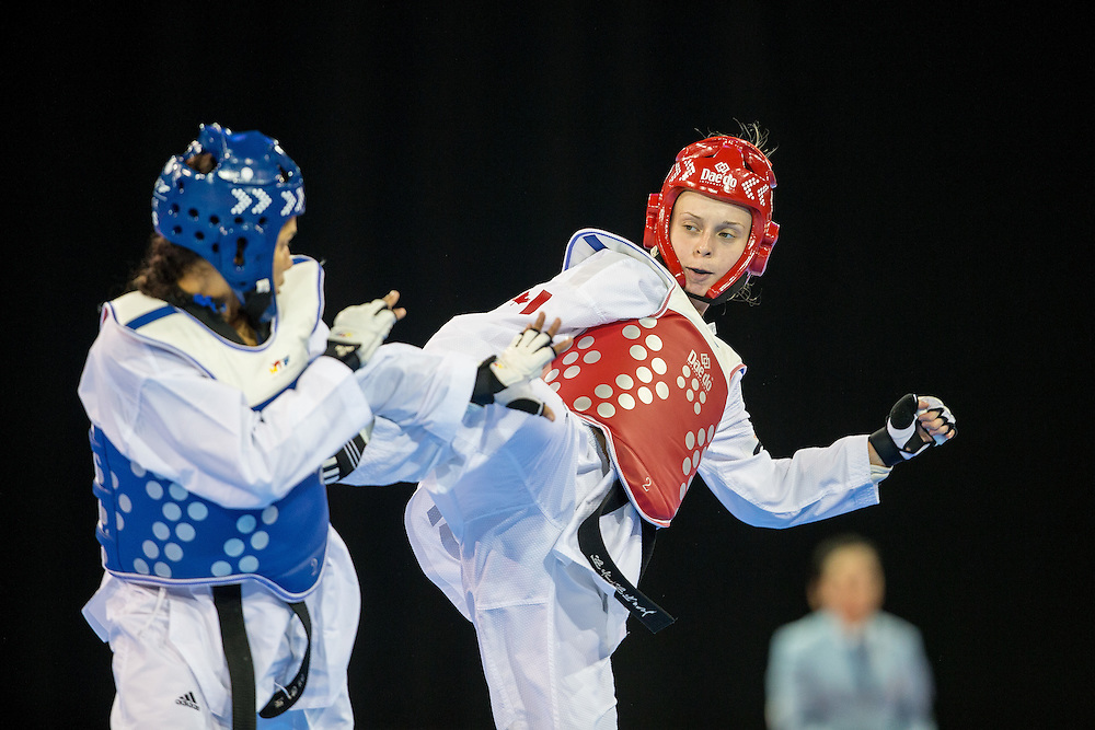 Evelyn Gonda of Canada kicks Disnansi Polanco of the Dominican Republic during their 1/8 round contest in the -57kg weight class of Taekwondo at the 2015 Pan American Games in Toronto, Canada, July 20,  2015.  AFP PHOTO/GEOFF ROBINS