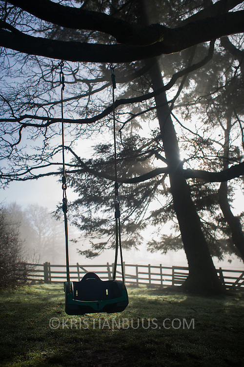 The sun breaks through morning mist over the hills in the Borders behind trees in a garden. An empty children's swing hangs of a branch, alone in the garden. The Southern parts of Scotland, the Borders, are rolling hills and mostly farm land.