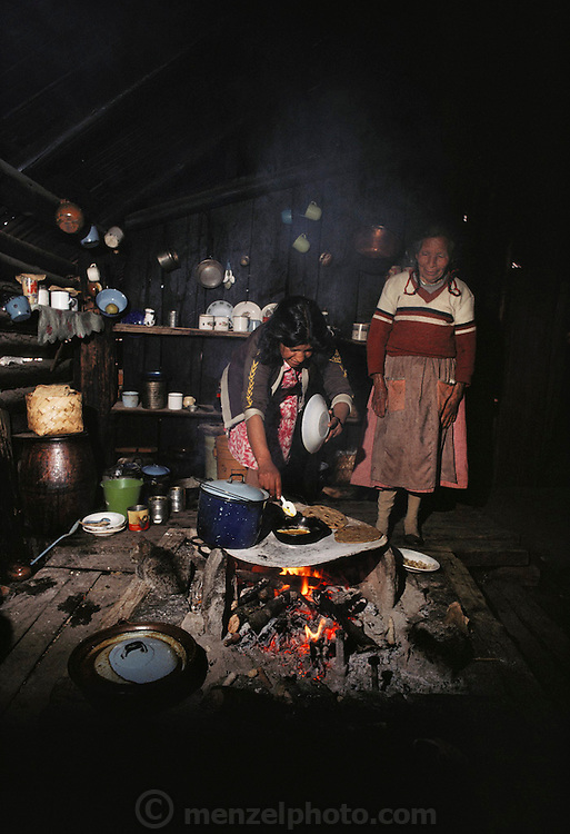 Two women prepare a meal on a wood fire in their ranch kitchen near the Monarch butterfly reserve. Site Alpha, near Rosario, Mexico.