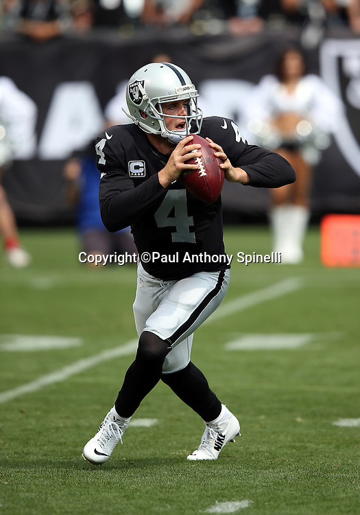 Oakland Raiders quarterback Derek Carr (4) scrambles and throws for a first quarter first down during the 2015 NFL week 1 regular season football game against the Cincinnati Bengals on Sunday, Sept. 13, 2015 in Oakland, Calif. The Bengals won the game 33-13. (©Paul Anthony Spinelli)