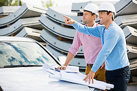 Architects with blueprints on car discussing at site