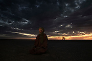 Brahim Mohamed Baih, 62, Polisario soldier, pictured praying in the desert in Polisario controlled Western Sahara near the Algerian border (Saharawi Arab Democratic Republic)...I was born in Tiris, which in now in the liberated territory of Western Sahara, in 1947. It is desert and a bedouin area with many camels. We traveled a lot to Zouerate in Mauritania when I was young. I was there in 1975 when Mauritania invaded Western Sahara. The Saharawi tried to move to the camps but they [Mauritanians] blocked the routes. I was arrested, they treated us badly. When Mauritania withdrew in 1979 Saharawis were then able to go to the refugee camps in Algeria. I was released and went also. It was an huge injustice, Mauritania had no right to be with Morocco, they had no reason to fight, no claim to the land. ..I fought in the war from '79, I had only the thought of freedom in my mind. In 1987 we captured eighty-seven Moroccan soldiers during an operation in Oumigata. We had a strong belief to win or die, our soldiers were strong; if not why do they build this wall? To protect themselves, without it they had no rest, we attacked them always...You fight to free your land and then sign a ceasefire and stop the fight. It was not a good idea. The United Nations are unjust, they know Morocco are unfair. Why don't they put pressure on them to solve this problem? I'm sure the UN will never solve this, it is better to free your land or to die. I am still a soldier and I work now in the liberated territory, I watch the wall and see the Moroccan soldiers moving and watching us. When I see them I wish I could carry out an operation to destroy them but politics is politics. I still return to Mauritania sometimes, they are friends of the Saharawi now and are on our side.