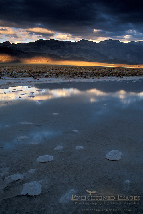 Storm clouds at sunset over Black Mountains and flooded salt pan, Devils Golf Course, Death Valley, California