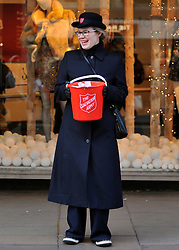 © Licensed to London News Pictures. 09/12/2011, London, UK. A Salvation Army collector sings carols to shoppers on Oxford Street. Christmas shoppers in London's Oxford Street and Regent Street today 09 December 2011. Some of the shops are already having sales and displaying prices in windows. Photo credit : Stephen Simpson/LNP