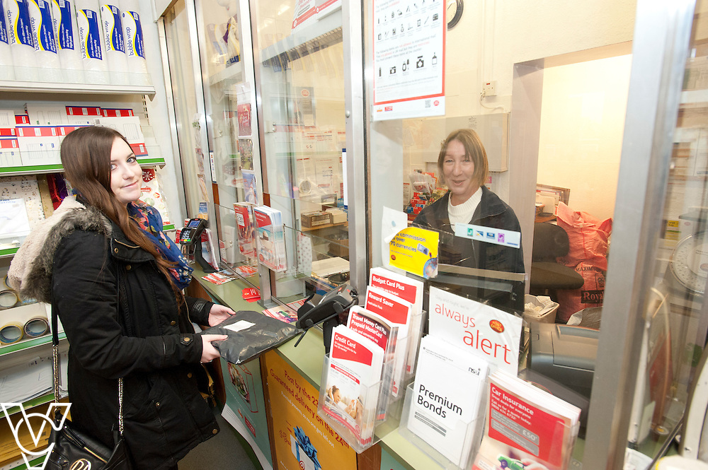 Pictured is postmaster Sarah Draisey serving customer Vicky Medlam<br /> <br /> Shireoaks Post Office, Worksop.  Community Fund feature.<br /> <br /> Date: December 1, 2014