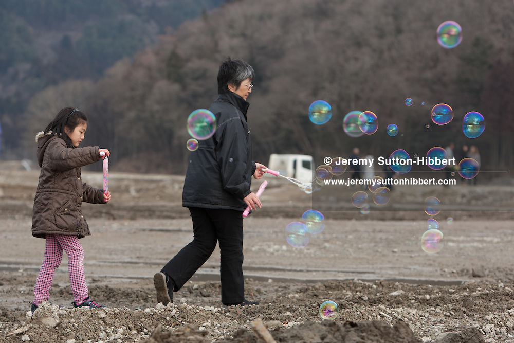 Hiroko Oyama and granddaughter Hikari release bubbles into the air for the memories of the 74 children who lost their lives at Okawa Elementary School, in the muddy plain where once stood the community of Kamaya, on the 1 year anniversary of the March 11th 2011 earthquake and tsunami, in Kamaya, Tohoku region, Japan on Sunday 11th March 2012.