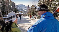 Two skiers walk through Whistler Village on a sunny winter day.