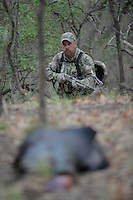 HUNTER APPROACHING A HARVESTED TURKEY