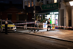 © Licensed to London News Pictures. 01/07/2019. London, UK.  Police officers at a crime scene outside 'Fair Food and Wine' convenience store. A man is fighting for his life in hospital having sustained puncture injuries to the neck in a fight with his younger brother. The victim in his 30s is understood to be in a critical condition following the assault. Police responded to a call at 5.12pm reporting a fight and attended an address in Argyle Road, West Ealing. Another man believed to be the victim's younger brother has been arrested. Photo credit: Guilhem Baker/LNP