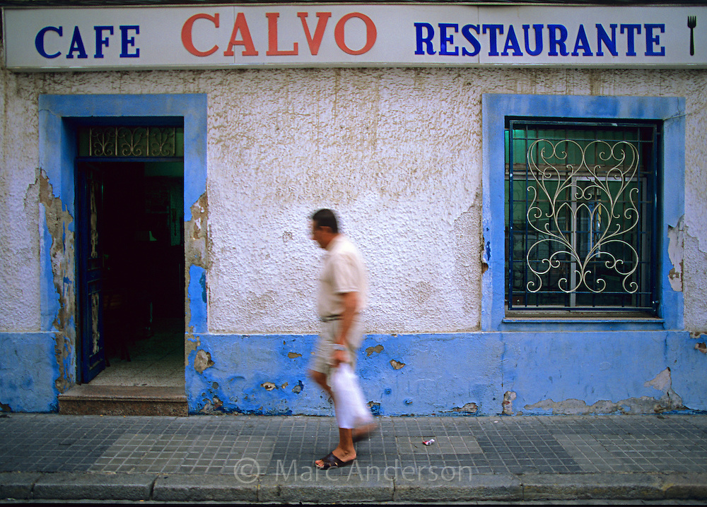 A man walking past a typical cafe in Huelva, Spain