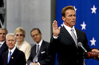 Arnold Schwarzenegger takes the oath of office as former Governor Gray Davis listens, on the steps of the Capitol in Sacramento.