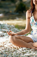Arm and leg of Young woman meditating by forest river cropped image