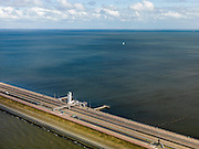Nederland, Noord-Holland, Gemeente Wieringen, 16-04-2012; Afsluitdijk ter hoogte van het Monument, de plaats waar in 1932 De Vlieter, het laatste gat, werd gesloten. De 32 kilometer lange dijk vormt de waterkering tussen Waddenzee (links) en IJsselmeer (rechts), aan de horizon is de kust van Friesland zichtbaar. Aanleg van de dijk vormde onderdeel Zuiderzeewerken, initiatief van ingenieur Cornelis Lely..Enclosure Dam at the height of the Monument, where in 1932 the Vlieter, the last opening, was closed. Frisian coast at the horizon (32 kilometers away).The dike forms the barrier between the Wadden Sea (left) and IJsselmeer lake (right), Frisian coast at the horizon (32 kilometers away)..luchtfoto (toeslag), aerial photo (additional fee required)..foto/photo Siebe Swart