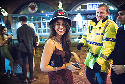 "© Licensed to London News Pictures . 19/12/2015 . Manchester , UK . A woman borrows a constable's helmet . Revellers in Manchester enjoy "" Mad Friday "" - also known as "" Black Eye Friday "" - the day on which emergency services in Britain are typically at their busiest , as people head out for parties and drinks to celebrate Christmas . Photo credit : Joel Goodman/LNP"