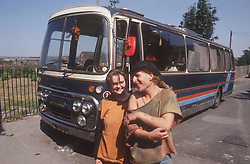 Travelling couple standing together smiling; with bus that they live in parked in background,