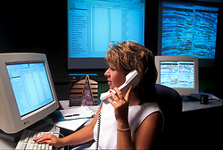 Stock photo of a business woman on the phone while typing on the computer keyboard