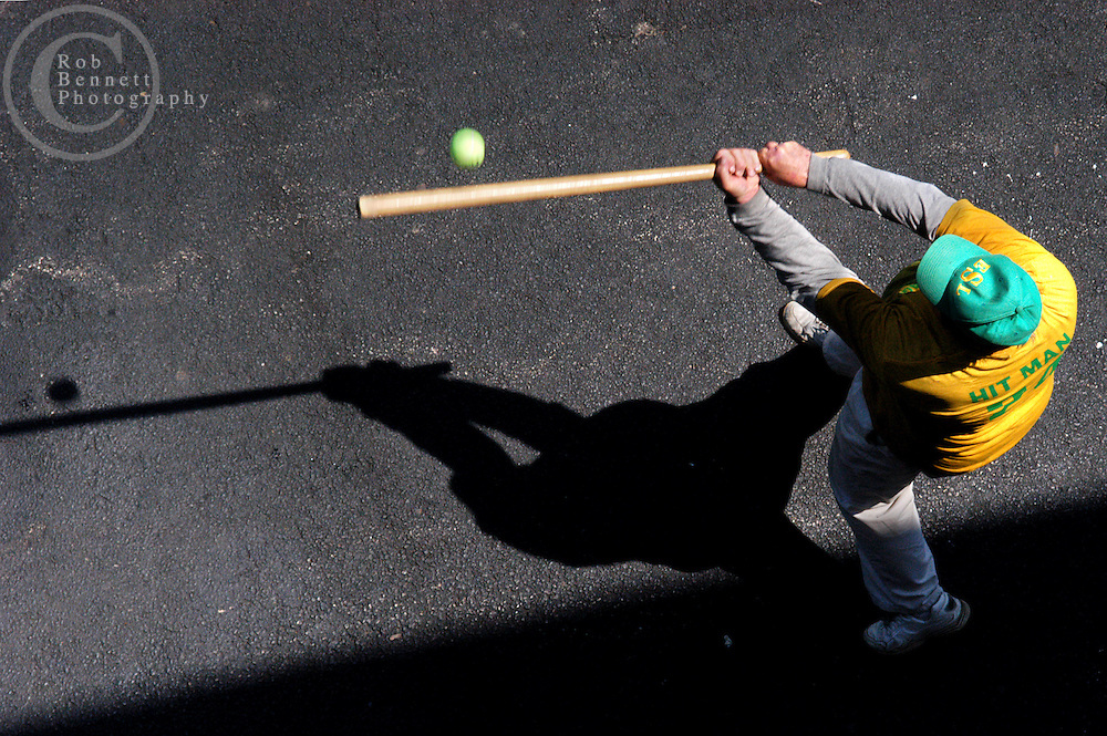 "Howard ""Hit Man"" Weishaus, 68 and a teacher from New City, bats during a game of stickball as seen from a second story school window..---.The Ethical Stickball League has been operating since 1970, meeting every Sunday in the parking lot behind Hastings High School from 10:30AM to 1PM.  The players are men now mostly in their 70s - carrying nicknames like ""The Wise One"", ""Hit Man"" and ""Plays Hurt"" - who have an affiliation with the school, either as former teachers, students or neighbors. As their slogan suggests, all it takes for a few hours of ""Aestas Aeterna"" (Eternal Summer) is an outside temperature above 45 degrees and 8 willing souls...CREDIT: Rob Bennett for The NY Times"