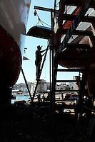 Particolare in controluce di un operaio al lavoro nel cantiere navale di Taranto.