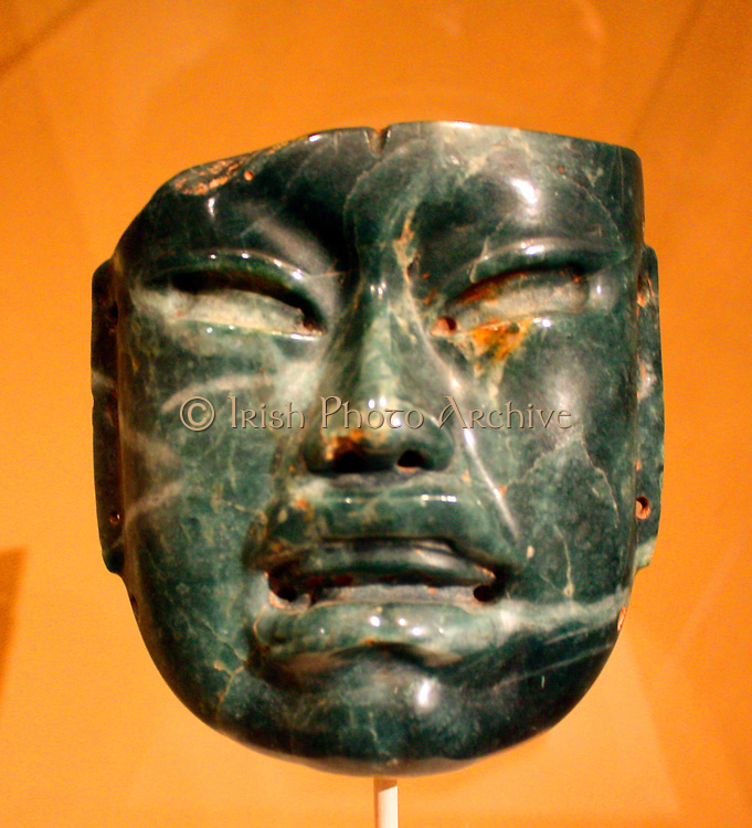 Olmec Mask.  Mexico, Olmec.  10th-6th century B C.  Jade (jadeite).  This mask, with its harmonious proportions and smooth, highly polished planes of cheek, forehead and chin has an almost fleshy quality of nose and lips that belies the incredible hardness of the jadeite cobble from which it is made.
