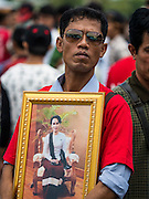 23 JUNE 2016 - MAHACHAI, SAMUT SAKHON, THAILAND:  A Burmese man waits for Aung San Suu Kyi to arrive in Samut Sakhon, a province south of Bangkok. Tens of thousands of Burmese migrant workers, most employed in the Thai fishing industry, live in Samut Sakhon. Aung San Suu Kyi, the Foreign Minister and State Counsellor for the government of Myanmar (a role similar to that of Prime Minister or a head of government), is on a state visit to Thailand. Even though she and her party won the 2015 elections by a landslide, she is constitutionally prohibited from becoming the President due to a clause in the constitution as her late husband and children are foreign citizens       PHOTO BY JACK KURTZ
