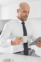 Mid adult businessman having coffee while using tablet PC in kitchen