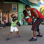 Natalie Baniea with a youngster during an afternoon boxing training session at the Hillbrow Boxing Club in Johannesburg, South Africa. As the club does not have the resources to provide child-size equipment, the youngsters make do with adult gloves. Located in one of the city's most notorious neighbourhoods, the club offers a de facto after school program for neighbourhood youngsters, providing camaraderie, discipline and an activity away from the streets. Some of the children who started out this way have gone on to become national champions.
