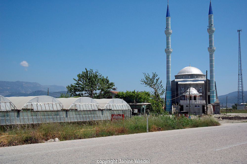 Mosque next to industrial greenhouses in village in Southern turkey.
