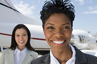 Portrait of mid-adult businesswoman standing in front of private plane.