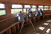 Birdwatchers in hide at Minsmere RSPB (Royal Society for the Protection of Birds) bird reserve, Suffolk, England