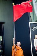 """06 MAY 2010 - BANGKOK, THAILAND:  A Buddhist monk waves a red flag in support of the Red Shirts Thursday in Ratchaprasong intersection. Red Shirt protestors in Ratchaprasong intersection, Thursday May 6, more than one month after the Reds occupied the intersection. Members of the United Front of Democracy Against Dictatorship (UDD), also known as the """"Red Shirts"""" and their supporters moved their anti government protests into central Bangkok Apr. 4 when they occupied Ratchaprasong intersection, the site of Bangkok's fanciest shopping malls and several 5 star hotels. The Red Shirts are demanding the resignation of current Thai Prime Minister Abhisit Vejjajiva and his government. The protest is a continuation of protests the Red Shirts have been holding across Thailand. They support former Prime Minister Thaksin Shinawatra, who was deposed in a coup in 2006 and went into exile rather than go to prison after being convicted on corruption charges. Thaksin is still enormously popular in rural Thailand. This move, away from their traditional protest site in the old part of Bangkok, has gridlocked the center of the city and closed hundreds of stores and restaurants and several religious shrines. On Thursday night the Red Shirt leaders said there has been a """"glitch"""" in the ongoing negotiations to end the standoff. Their opponents, the """"Yellow Shirts"""" who previously supported the incumbent Prime Minister have rejected his peace plan and called for the PM to resign.  PHOTO BY JACK KURTZ"""