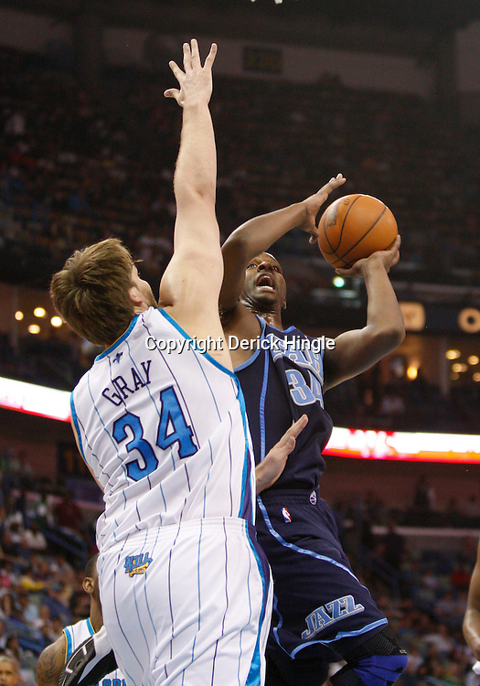 Apr 09, 2010; New Orleans, LA, USA; Utah Jazz forward C.J. Miles (34) shoots over New Orleans Hornets center Aaron Gray (34) during the first half at the New Orleans Arena. Mandatory Credit: Derick E. Hingle-US PRESSWIRE
