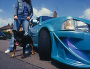 A girl with a Pitbull terrier, stood next to a customised car, UK, 2000's