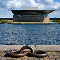 Opera House Seen from Quay in Copenhagen, Denmark <br /> The Copenhagen Opera House is a neo-futurism building that opened in 2004 on the island of Holmen in a waterfront section called Dokøen. The half billion dollar construction cost was a gift of the Møller Foundation. Operaen på Holmen is seen here from across the harbor.  In the foreground are mooring rings along the Kvæsthusbroen quay.