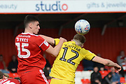 Accrington Stanley defender Ross Sykes (15) and Fleetwood Town defender Cian Bolger (12) battle for a header during the EFL Sky Bet League 1 match between Accrington Stanley and Fleetwood Town at the Fraser Eagle Stadium, Accrington, England on 30 March 2019.