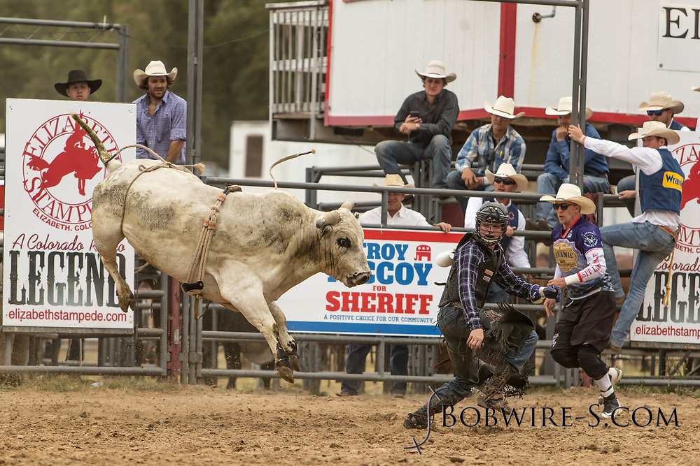 Bullfighters Nate Jestes (light shirt) and Cade Burns come to the aid of bull rider Colten Beaty after his ride on Summit Pro Rodeo's Kingsman during the third performance of the Elizabeth Stampede on Sunday, June 3, 2018.