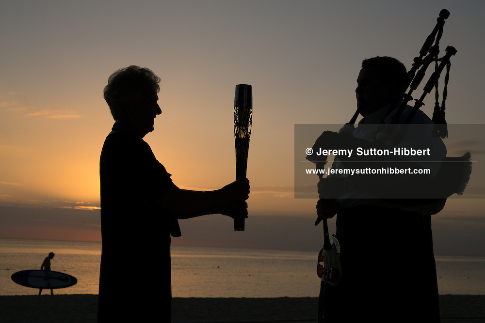 The Queen's Baton held by Louise Martin of the Commonwealth Games Federation (left) and and bagpiper Alastair Bird, in Cayman Islands, Monday 14 April 2014. Cayman Islands is nation 55 of 70 nations and territories the Queen's Baton will visit.