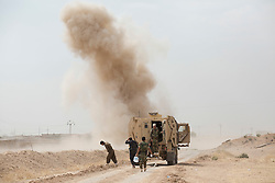 © Licensed to London News Pictures. 30/09/2015. Kirkuk, Iraq. Kurdish peshmerga EOD technicians are seen with their armoured vehicle after detonating one of many IEDs around the village of Mansoria near Kirkuk, Iraq.<br /> <br /> Supported by large amounts of coalition airstrikes, members of the Iraqi-Kurdish peshmerga today (30/09/2015) took part in an offensive to take seven villages across a large front near Kirkuk, Iraq. By mid afternoon the Kurds had reached most of their objectives, but suffered around 10 casualties all to improvised explosive devices. All seven villages were originally Kurdish and settled with other ethnic groups during the Iraqi Arabisation process of the 1970's and 80's. Photo credit: Matt Cetti-Roberts/LNP