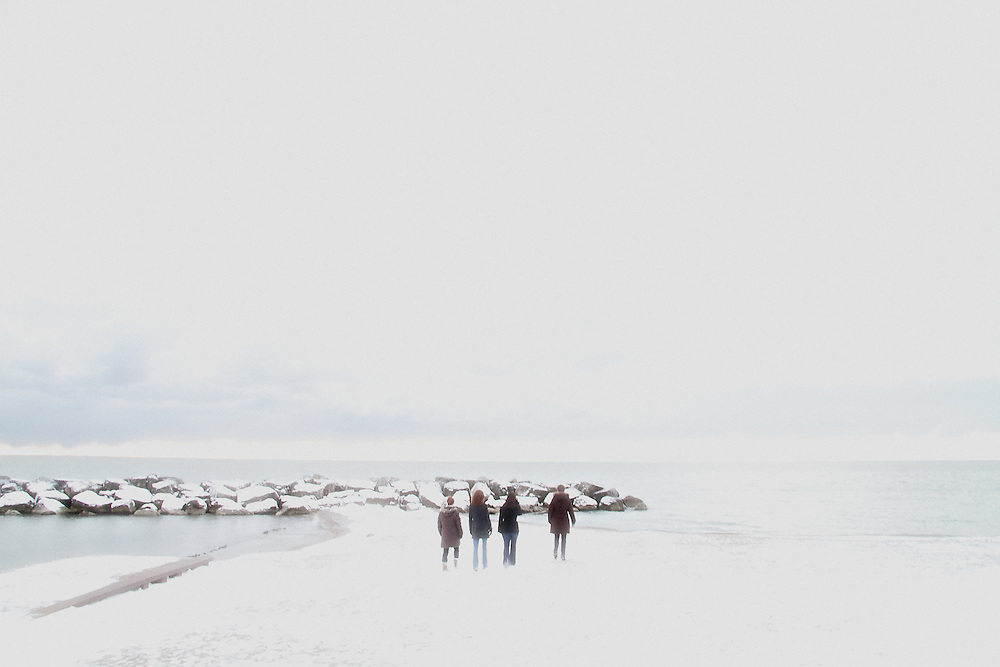 Four people walk along a wintery shore in the Beaches neighbourhood of Toronto, Canada.