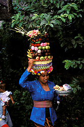 Indonesian Woman, Bali, Indonesia, Asia, photo bali218, Photo Copyright:  Lee Foster, www.fostertravel.com, 510-549-2202, lee@fostertravel.com, native, indonesian, woman, basket, fresh fruit, flora, flowers, young child, vertical