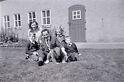 family posing on the grass in front of the farmhouse 1960s