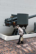 Tokyo, April 10 2014 - An old man walking in front of a cannon on display at the Yushukan, Yasukuni's war museum.