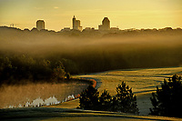 The sun rises over downtown Raleigh and a foggy Lonnie Poole Golf Course.